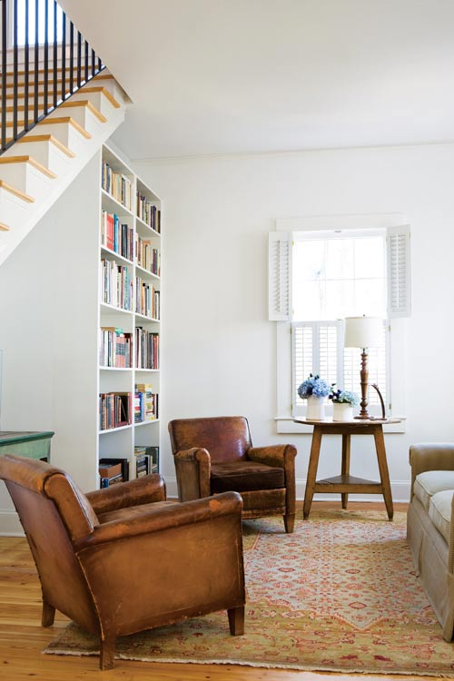 In the family room, built-in storage keeps clutter to an absolute minimum. Bookshelves were built where an awkward wall of doors had once been, and a triangular cabinet under the stairwell allows the children's toys to be stowed away easily. Leather club chairs, Scott Antique Market. The cricket table belonged to Andrew's parents.