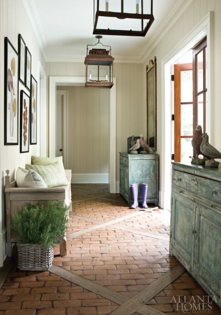 In the back entry hall, Morris brings the outdoors inside with brick flooring, botanical prints, iron lanterns from South of Market, and a pair of weathered Catalan chests leading out to the pool.