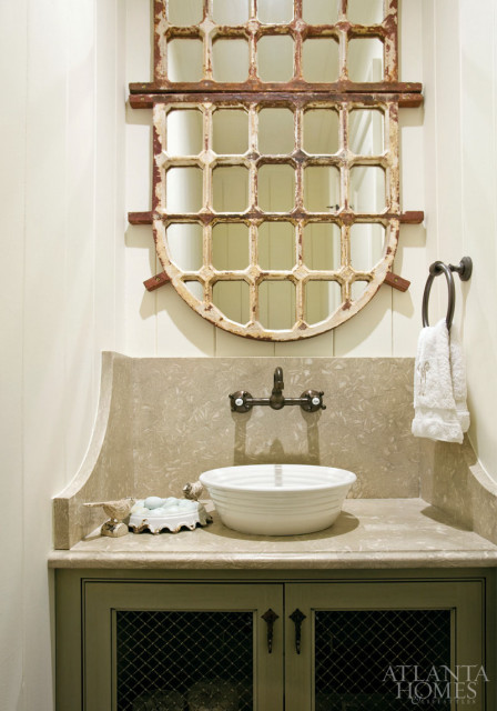 One of the home's powder rooms features a pair of arched iron windowpane mirrors placed together to look like one; the vanity is topped with linden green limestone.