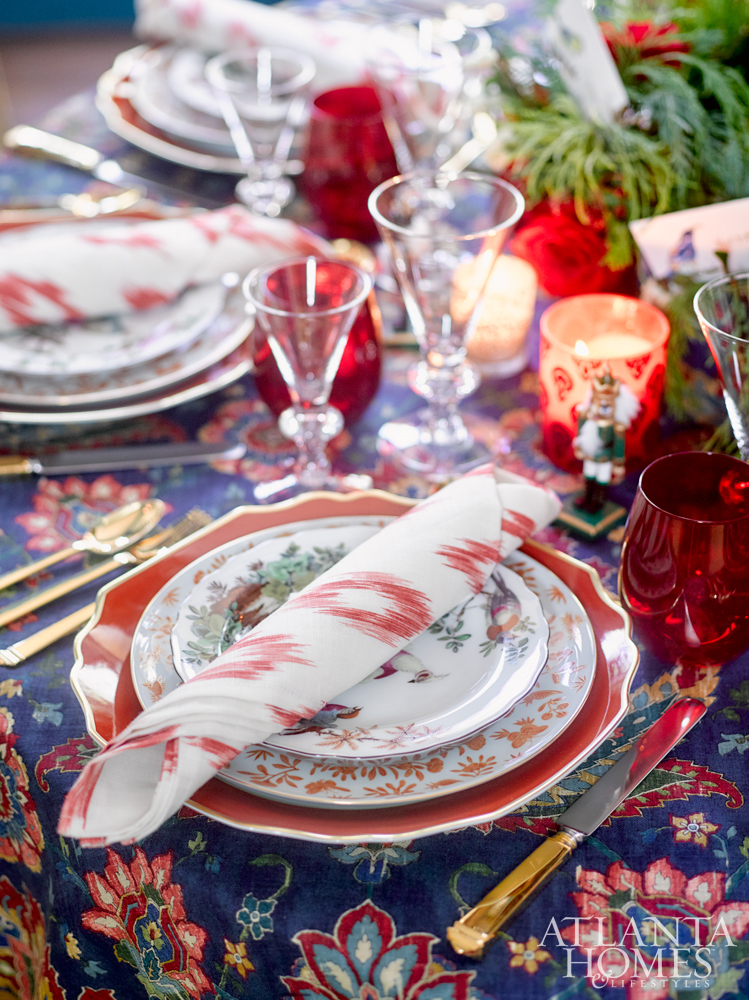 Bright red and blue elegant placesetting at Christmas table with red glasses