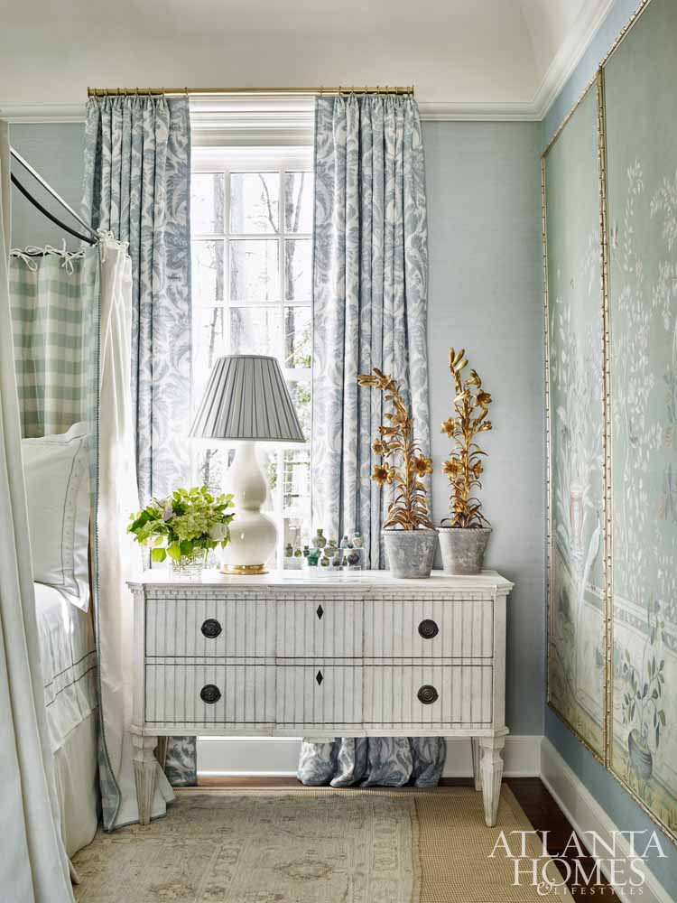 Elegant traditional blue bedroom with painted panels, blue drapes, and brass hardware